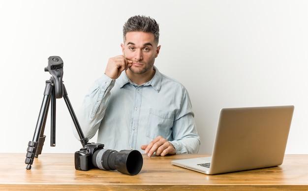 Jeune beau professeur de photographie avec les doigts sur les lèvres gardant un secret.