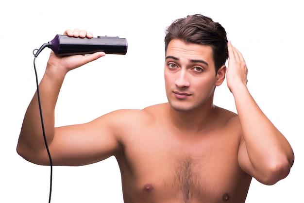Jeune beau séchant ses cheveux isolé sur blanc