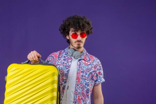 Jeune beau voyageur bouclé homme portant des lunettes de soleil et des écouteurs sur le cou tenant la valise regardant à droite sur un mur violet isolé avec copie espace