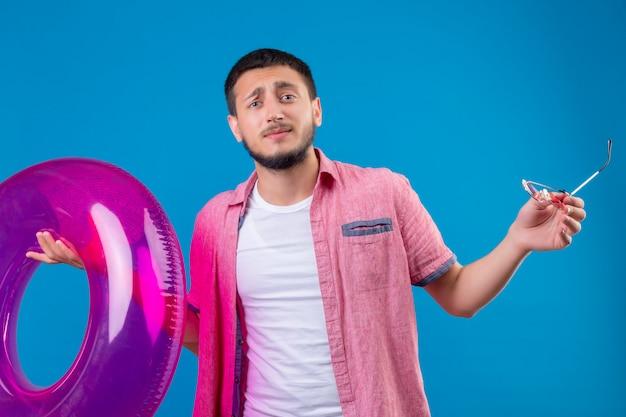 Jeune beau voyageur guy holding anneau gonflable désemparé et confus regardant la caméra n'ayant pas de réponse répandre les mains debout sur fond bleu