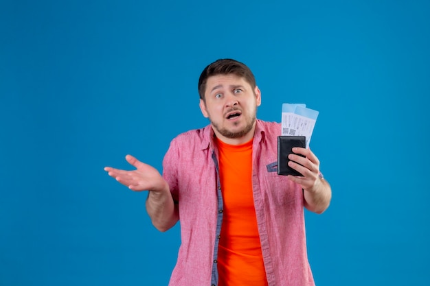 Jeune beau voyageur homme tenant des billets d'avion désemparés et confus étalant les bras n'ayant pas de réponse debout sur le mur bleu