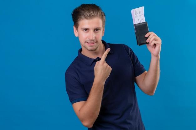 Jeune beau voyageur homme tenant des billets d'avion doigt pointé vers eux heureux et positif regardant la caméra avec un sourire confiant sur le visage debout sur fond bleu