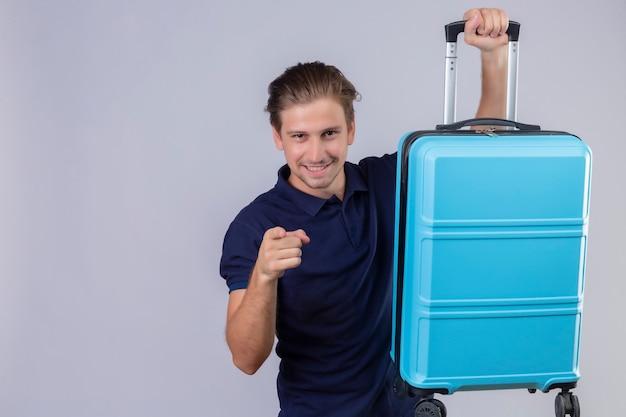 Jeune beau voyageur homme tenant valise à la caméra à doigt pointé confiant souriant debout sur fond blanc