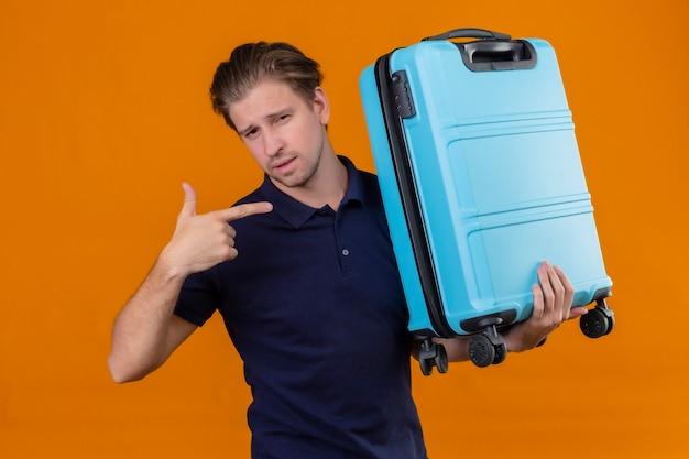 Jeune beau voyageur homme tenant valise à la recherche de doigt pointé confiant debout sur fond orange