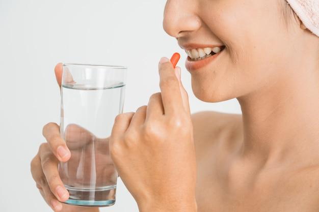 Jeune beauté asiatique jeune femme mangeant des pilules et de l'eau potable sur un mur blanc.