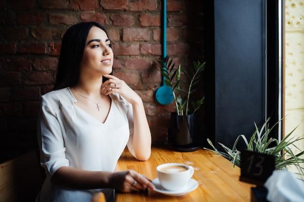 Jeune beauté femme buvant du café dans un café en plein air.
