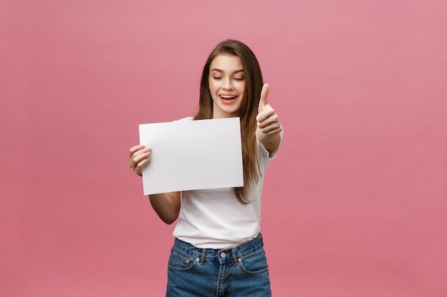 Jeune beauté femme détiennent une carte vierge et montrant les pouces vers le haut sur fond rose