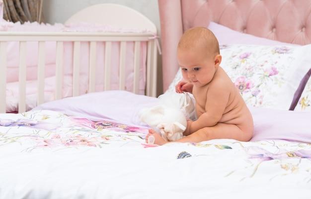 Jeune bébé au visage sérieux joue avec un jouet assis sur le lit sans vêtements, tourné sur toute la longueur dans la chambre des parents avec espace copie
