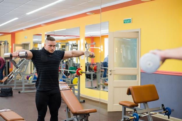Jeune bel athlète dans la vieille salle de gym rouillée