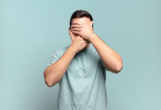 Jeune bel homme adulte couvrant le visage avec les deux mains disant non à la caméra ! refuser des photos ou interdire des photos