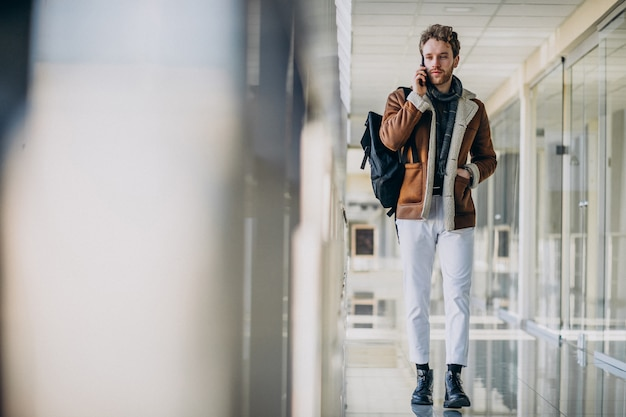 Jeune bel homme à l'aéroport, parler au téléphone