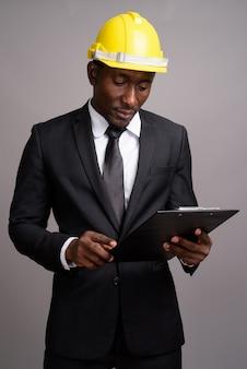 Jeune bel homme d'affaires africain avec casque contre bac gris