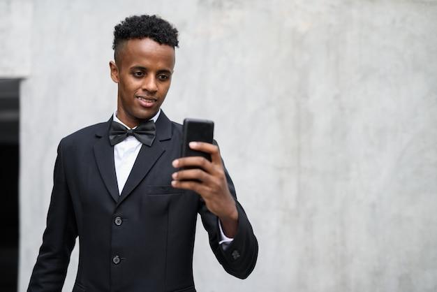 Jeune bel homme d'affaires africain portant un costume contre le béton