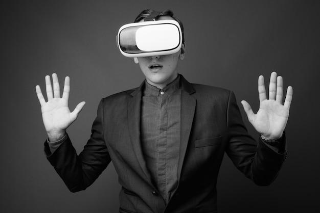 Jeune bel homme d'affaires à l'aide d'un casque de réalité virtuelle contre un mur gris. noir et blanc