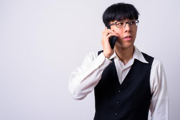 Jeune bel homme d'affaires asiatique contre le mur blanc