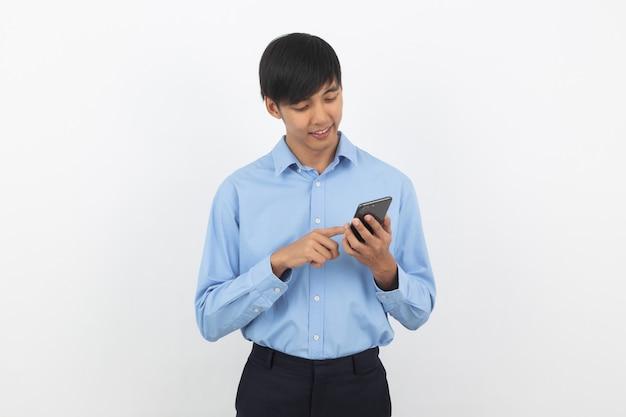 Jeune bel homme d'affaires asiatique jouant smartphone avec sourire isolé sur blanc