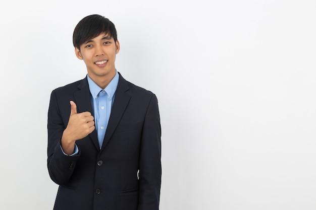 Jeune bel homme d'affaires asiatique souriant et montrant les pouces vers le haut isolé sur mur blanc.