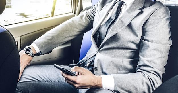 Jeune bel homme d'affaires assis dans un taxi tout en envoyant des sms avec smartphone