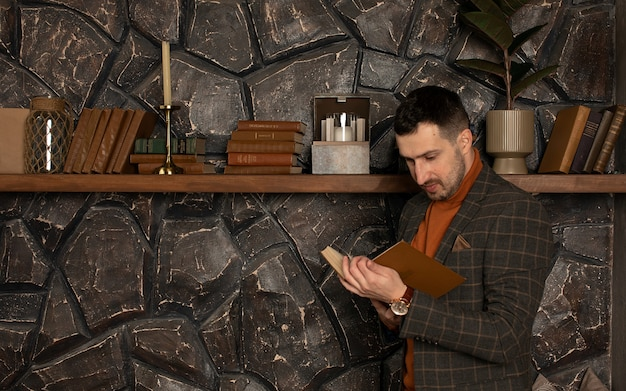 Jeune bel homme d'affaires avec barbe en costume livre de lecture
