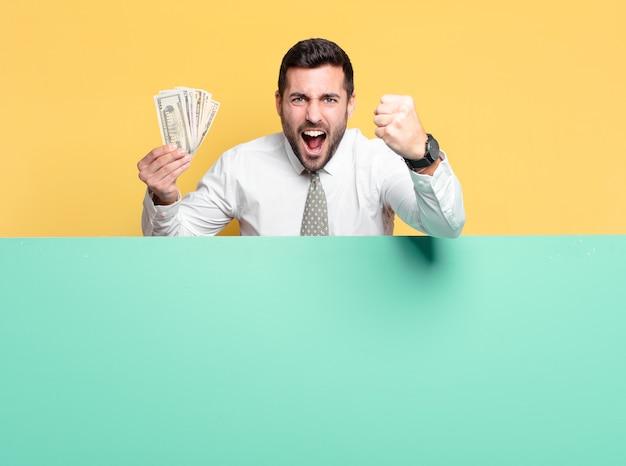 Jeune bel homme d'affaires avec des billets en dollars