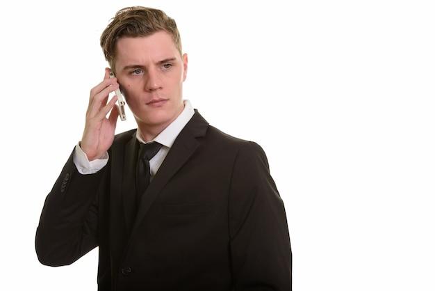 Jeune bel homme d'affaires blonde en costume à l'aide de téléphone