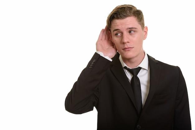 Jeune bel homme d'affaires blonde en costume à l'écoute
