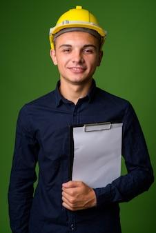 Jeune bel homme d'affaires avec casque sur fond vert
