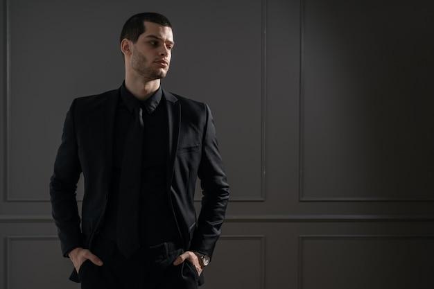 Jeune bel homme d'affaires en chemise noire et costume noir
