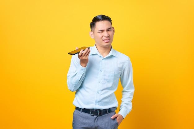 Jeune bel homme d'affaires confus parlant sur un smartphone sur fond jaune