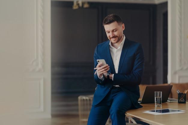 Jeune bel homme d'affaires en costume bleu foncé formel regardant un smartphone et souriant tout en lisant des messages, assis avec désinvolture sur un bureau dans un bureau minimaliste élégant ou travaillant à domicile