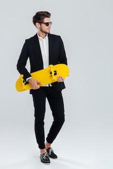 Jeune bel homme d'affaires en costume et lunettes tenant une planche à roulettes jaune sur un mur gris
