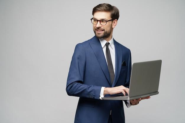 Jeune bel homme d'affaires détenant un ordinateur portable avec écran blanc