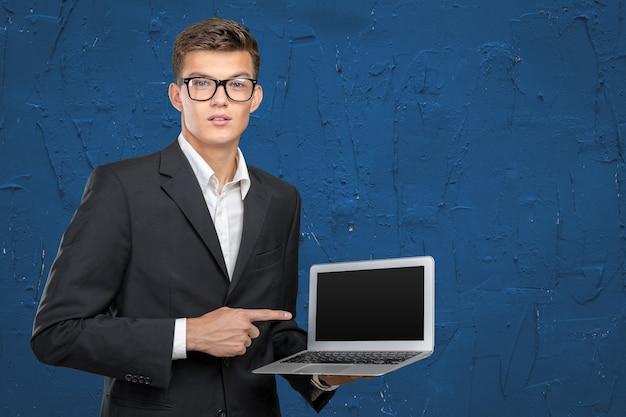 Jeune bel homme d'affaires détenant un ordinateur portable