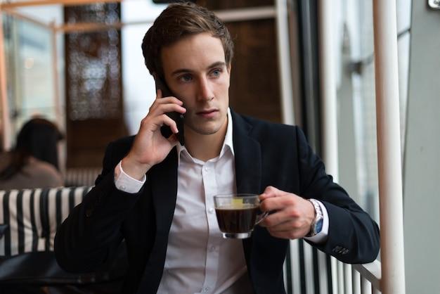 Jeune bel homme d'affaires avec du café, parler au téléphone au café