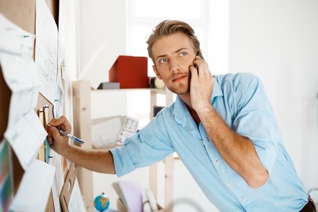 Jeune bel homme d'affaires, écrivant au papier épinglé au tableau de liège, parler au téléphone.