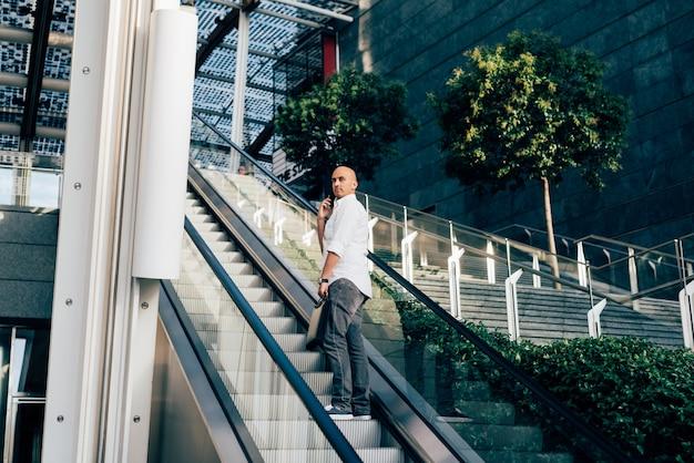 Jeune bel homme d'affaires sur un escalator