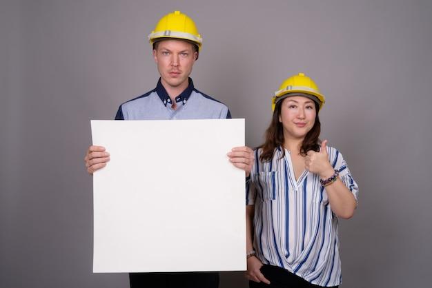 Jeune bel homme d'affaires et femme d'affaires asiatique mature portant un casque