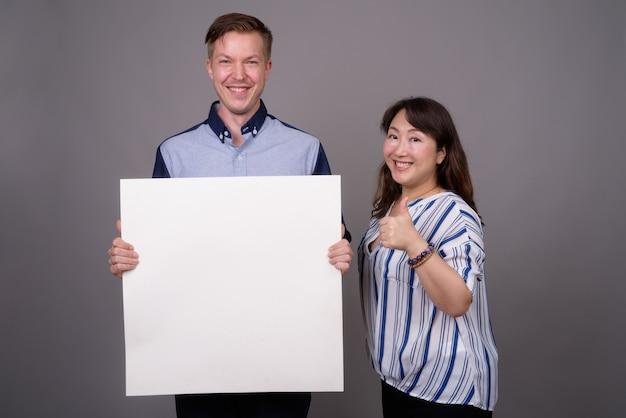 Jeune bel homme d'affaires et femme d'affaires asiatique mature
