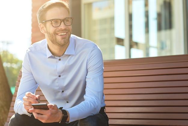 Jeune bel homme d'affaires heureux portant une chemise bleue et des lunettes à l'aide d'un smartphone et souriant