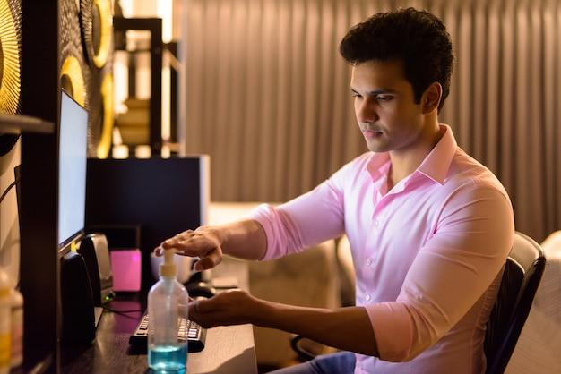 Jeune bel homme d'affaires indien à l'aide de désinfectant pour les mains tout en travaillant des heures supplémentaires à la maison pendant la quarantaine