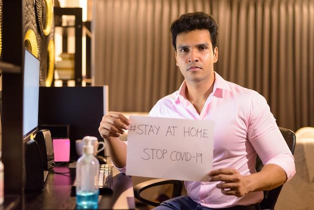 Jeune bel homme d'affaires indien montrant rester à la maison signe tout en travaillant des heures supplémentaires à la maison pendant la quarantaine