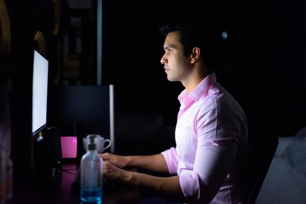 Jeune bel homme d'affaires indien travaillant des heures supplémentaires à la maison pendant la quarantaine dans l'obscurité