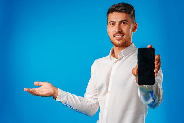 Jeune bel homme d'affaires montrant l'écran du smartphone noir sur fond bleu close up