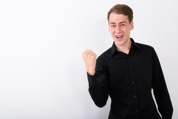 Jeune bel homme d'affaires sur mur blanc
