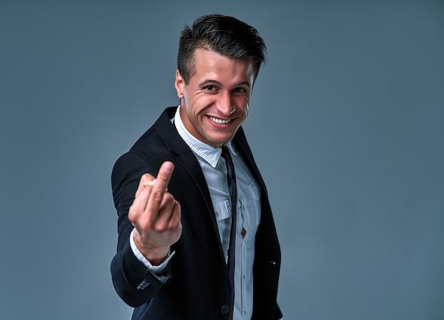 Jeune bel homme d'affaires portant un costume et une cravate, debout sur un fond gris isolé, montrant le doigt du milieu, une expression impolie et grossière.