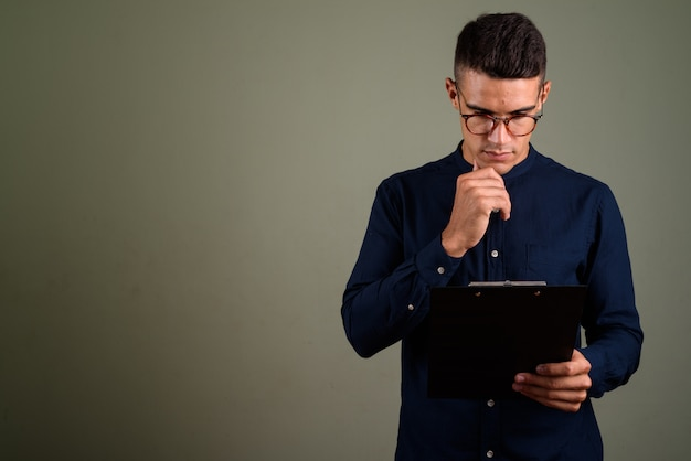 Jeune bel homme d'affaires portant des lunettes contre ba de couleur