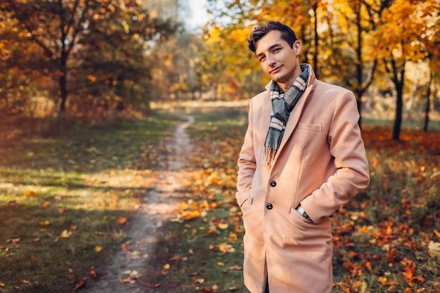 Jeune bel homme d'affaires portant des vêtements classiques et des accessoires dans la forêt d'automne au coucher du soleil