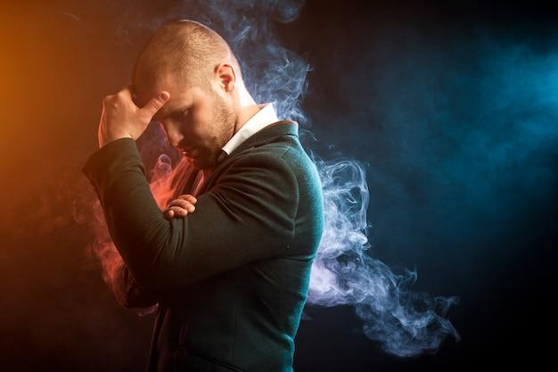 Jeune bel homme d'affaires posant contre la fumée rouge et bleue