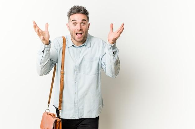 Jeune bel homme d'affaires recevant une agréable surprise, excité et levant les mains.