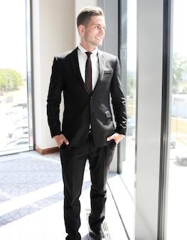 Jeune bel homme d'affaires souriant dans un environnement de bureau